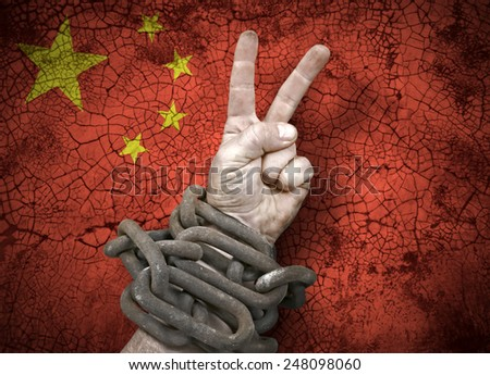 Independence: hand victory sign in chains and the flag of China - stock photo