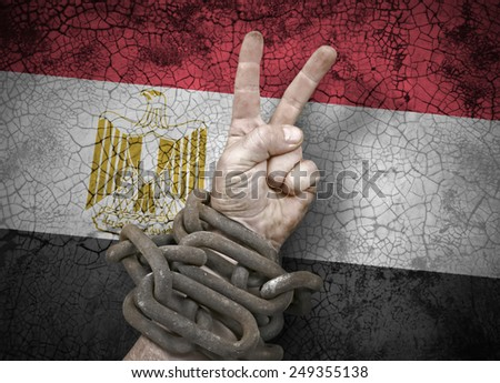 Independence: hand victory sign in chains and the flag of Egypt - stock photo