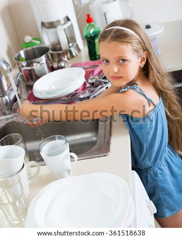 Independent beauty little girl doing dishes at kitchen