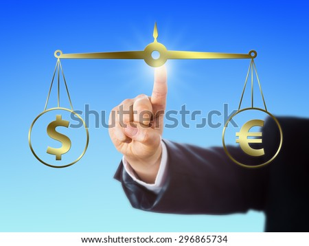 Index finger is equating the Dollar sign at par with the Euro symbol on a golden pair of balances. Right arm of a trader reaching forward to position this virtual weighing scale in space. Close up. - stock photo