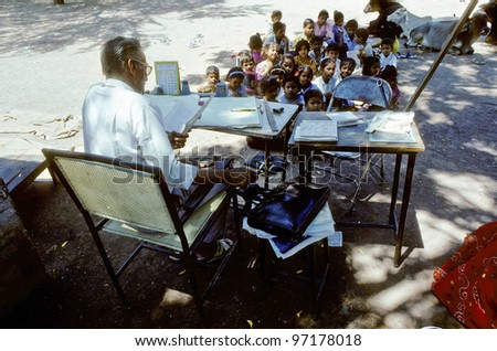 INDIA, AGRA - AUGUST 01: teacher in the outdoor school class on August 01,1994 in Agra, India. The number of pupils attending school increases from around 19.2 million in 1950 to 114 million in 2002. - stock photo