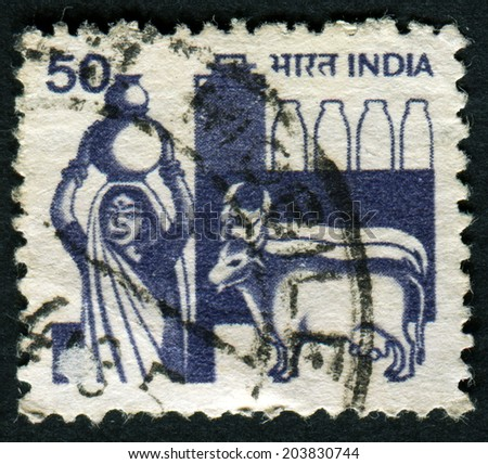 INDIA - CIRCA 1965: A stamp printed by India shows Woman with a jug of milk and two cows, circa 1965 - stock photo