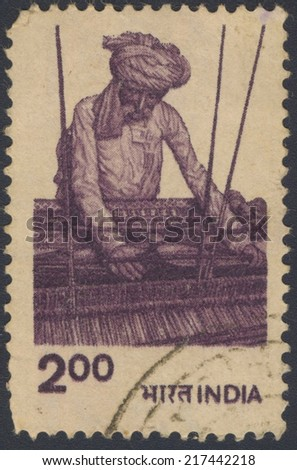 INDIA - CIRCA 1961: A stamp printed in India shows old man weaves a carpet, circa 1961. - stock photo