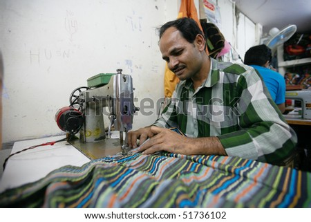 INDIA - FEB 26: Textile worker in a small factory in Old Delh on February 26, 2008 in Delhi, India. Many small factories provide the West with their clothes. - stock photo