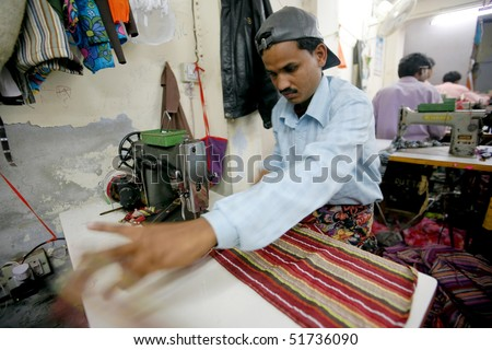 INDIA - FEB 26: Textile worker in a small factory in Old Delhi on February 26, 2008 in Delhi, India. Many small factories provide the West with their clothes. - stock photo