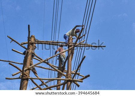 INDIA, HIMACHAL PRADESH, 2015-10-29: Construction of a high-voltage power line in the country side near Roorkee. Workers preparing cables on a wooden construction to cross a road safely