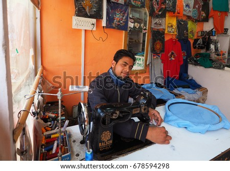 India - June 18 2017: Man sewing in cloth shop in leh main bazaar Leh Ladakh - India