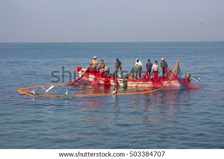 India, Kerala - December 27, 2015: Indians (fishermen cooperative) graphically pull painted Seine in boat. Mutualism: fishermen collect fish in seine, and little egrets eat and don't let it in sea