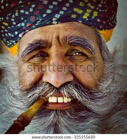 India Man Smoking Pipe Solitude Tranquil Wisdom Concept - stock photo