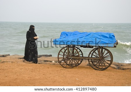 India Puducherry trolley with muslim woman walking by on the beach by the ocean - stock photo