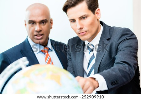 Indian and Caucasian business men discussing offshoring project looking at globe exploring new markets - stock photo
