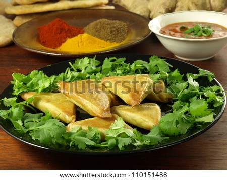 Indian appetizer: vegetable samosas with dip and hot spices - stock photo