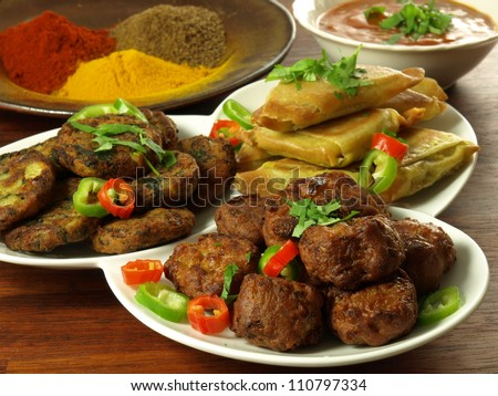 Indian appetizers with bowl of dip and spices - stock photo
