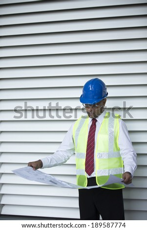 Indian Architect or engineer at work on a building site. Checking plans against the construction work. - stock photo