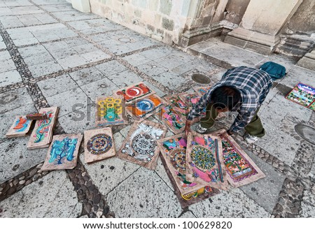 Indian artist sells paintings in front of the Santo Domingo Church - Oaxaca, Mexico - stock photo