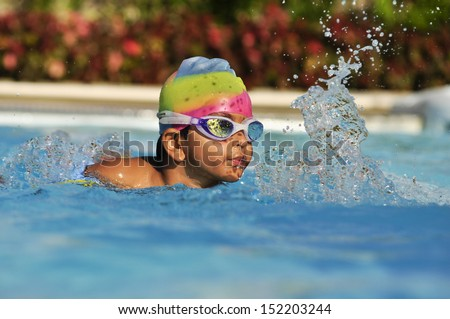 Indian asian Boy in the swimming pool with goggles in Arab resort - stock photo