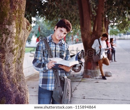 Indian / Asian college student studying while waiting in the campus parking. - stock photo