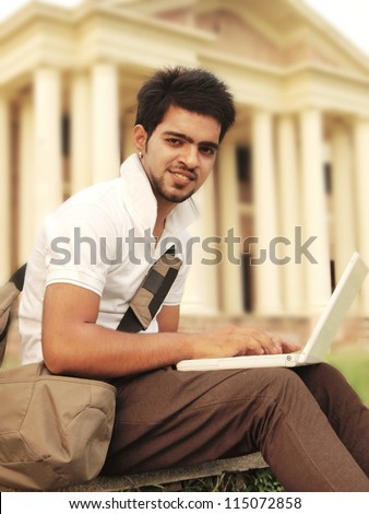 Indian / Asian college student working on laptop computer in campus . - stock photo