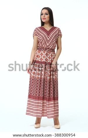 indian asian eastern brunette business executive woman with straight hair style in printed ethnic summer long dress high heel shoes standing full body length isolated on white - stock photo