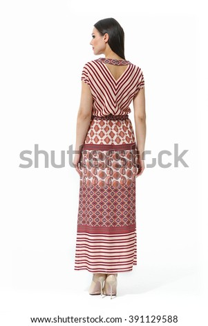 indian asian eastern brunette business executive woman with straight hair style in printed ethnic summer long dress high heel shoes standing full body length isolated on white back view - stock photo