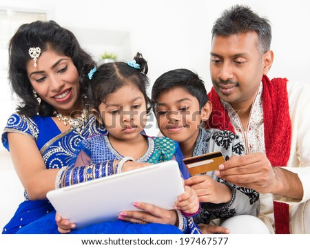 Indian Asian family using digital tablet pc computer online shopping with credit card at home. India family living lifestyle.