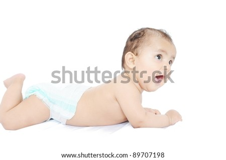 Indian baby laying on bed.