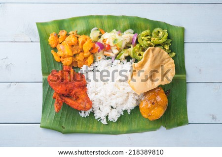 Indian banana leaf rice, overhead view on wooden dining table. - stock photo