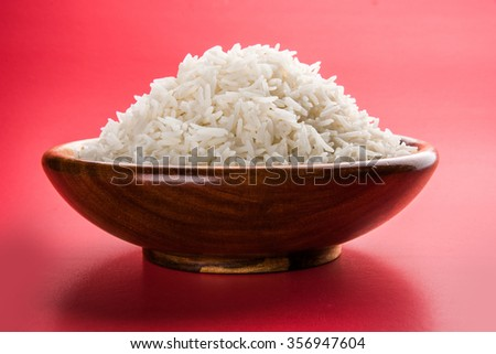 indian basmati rice, pakistani basmati rice, asian basmati rice, cooked basmati rice, cooked white rice, cooked plain rice in wooden bowl over red background - stock photo
