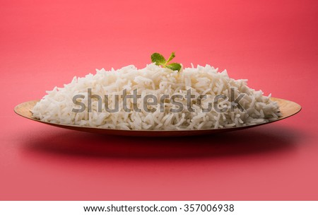 indian basmati rice, pakistani basmati rice, asian basmati rice, cooked basmati rice, cooked white rice, cooked plain rice in oval brass bowl over red background  - stock photo