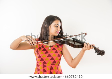 Indian beautiful young girl playing violin while standing over white background