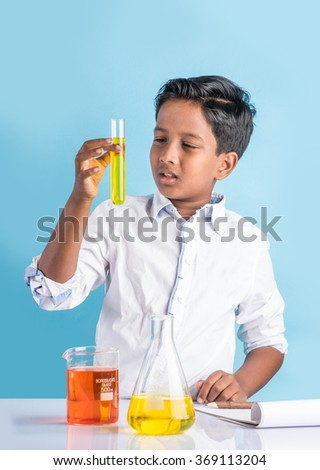 indian boy and chemistry experiment, asian boy doing chemistry experiment, indian boy and science experiment, boy with test tube - stock photo