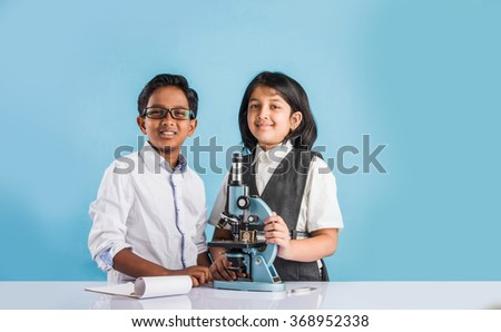 indian boy and girl withmicroscope, asian kids with microscope, Cute little kids holding microscope, 10 year old indian boy and girl and science experiment, school students doing science experiments - stock photo