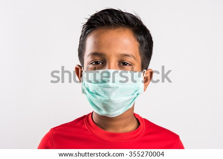 indian boy and medical mask, asian boy wearing green medical mask, 10 year old boy with mask looking straight, boy with safety mask,isolated on white background - stock photo