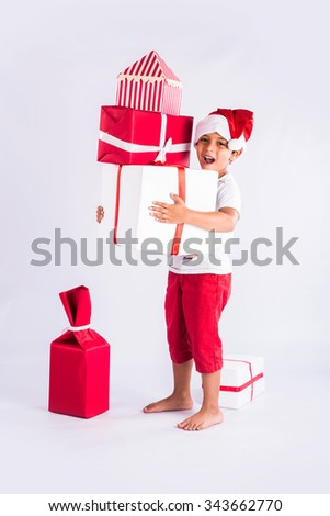 indian boy holding christmas gifts stacked in both hands, wearing christmas hat, santa hat,indian kid and christmas, asian boy, indian boy, asia and christmas - stock photo