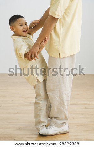Indian boy standing on father's feet - stock photo