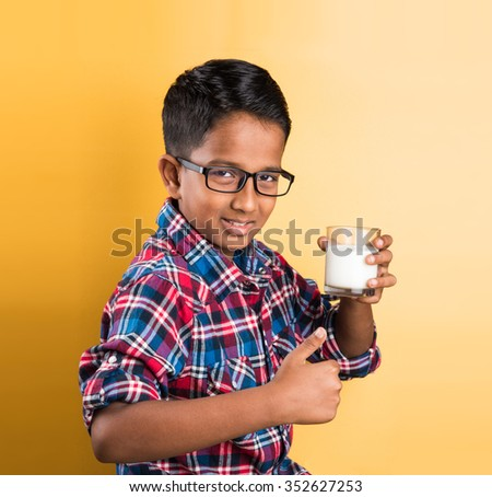 indian boy with a glass of milk, indian kid drinking milk, indian boy drinking milk,asian boy and milk, closeup portrait on yellow background