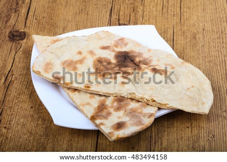 Indian bread naan in the plate on wood background