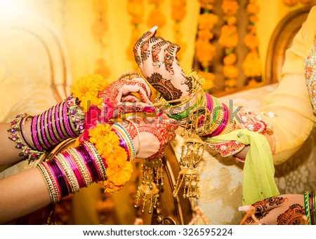 Indian bride hands getting decorated. - stock photo