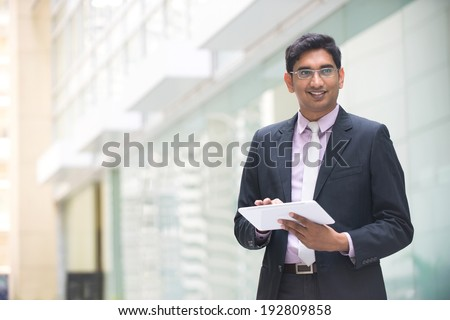 indian business executive working on tablet computer in office with copyspace on left - stock photo