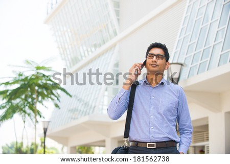 indian business male on a phone with office background - stock photo