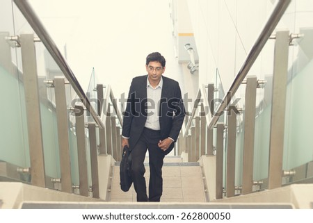 indian business male walking on stairs - stock photo