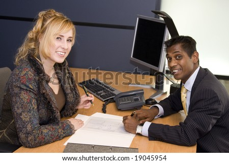 Indian Business Man and Caucasian Woman Signing a Contract - stock photo