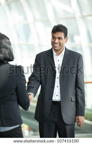 Indian business man and woman shaking hands. - stock photo