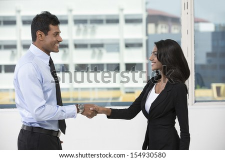 Indian business man and woman shaking hands in the office. Cheerful Asian colleagues or client greeting each other. - stock photo