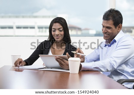 Indian business man and woman using a digital tablet while having a meeting. - stock photo