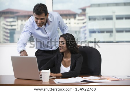Indian business man and woman working together at a desk in an office - stock photo