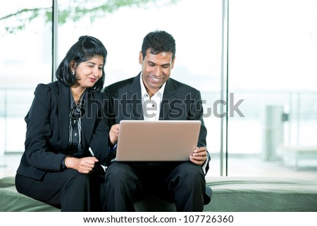 Indian Business man and woman working together on a laptop - stock photo
