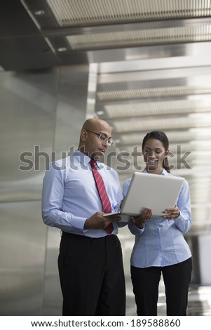 Indian business Man and woman working together on a laptop outdoors in modern city. - stock photo