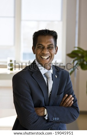 Indian Business Man Laughing with Arms Folded Indoors