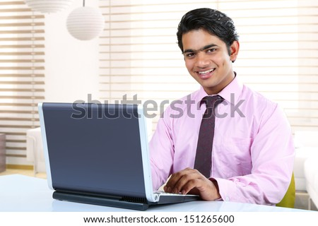 Indian Business man sitting at his desk  with a laptop - stock photo